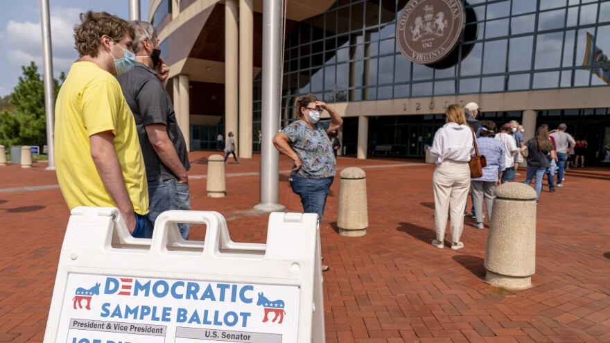 A Democratic sample ballot is on display as hundreds wait in line for early voting at Fairfax County Government Center on Friday in Fairfax, Va.