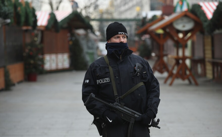 A police officer stands guard Wednesday near a Christmas market in Berlin where a truck plowed into a crowd Monday, killing 12 people.