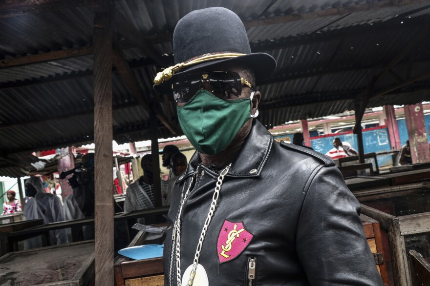 A <em>Sapeur</em> — as Congolese fashionistas are known — shows off his mask at a market in Kinshasha.