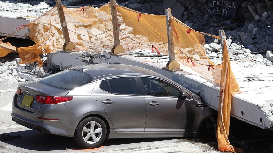 A crushed car sits under a section of a collapsed pedestrian bridge on Friday near Miami. Authorities are still investigating the cause.