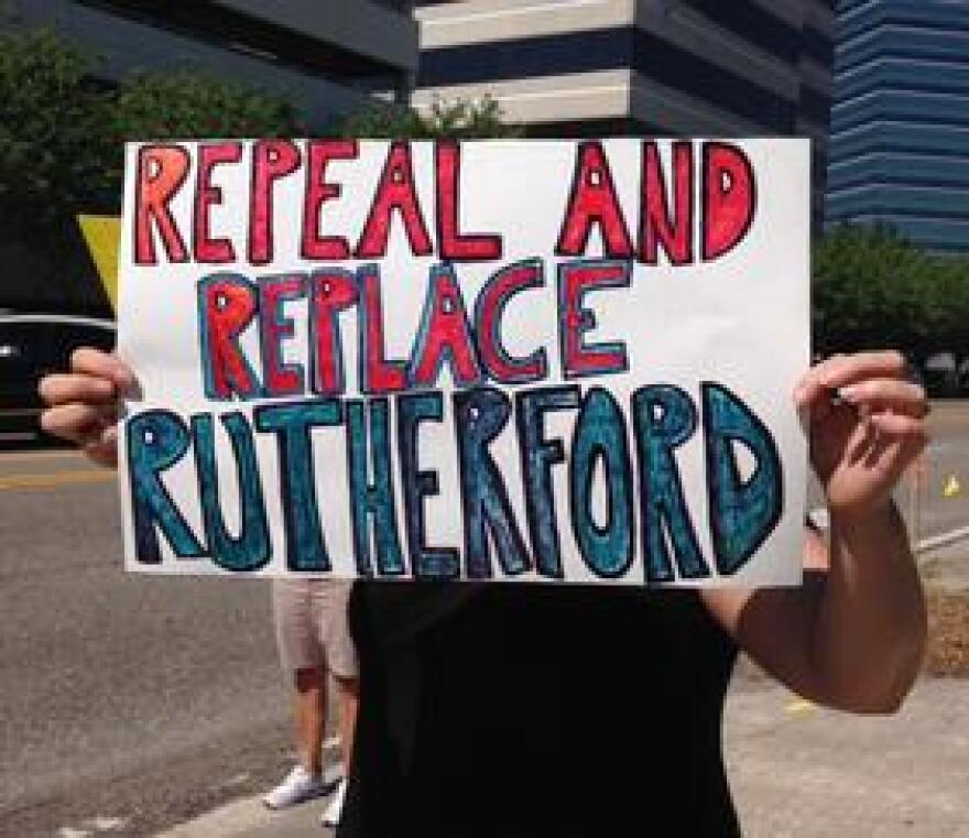 A protester holds up a sign outside Ruth Chris Steakhouse on Riverplace Boulevard on Jacksonville's Southbank.