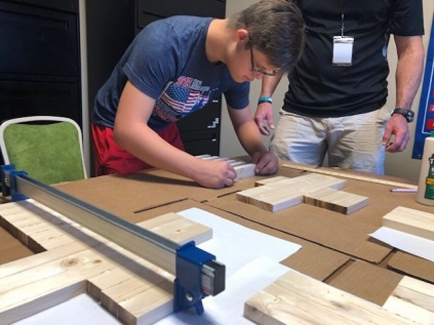 Kason Kolka is bent over a table next to David Kelly with various shapes of wood. He's helping create artwork for the VIP silent auction at The Producers concert later this month.
