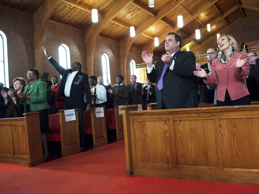 New Jersey Gov. Chris Christie joins Lt. Gov. and Secretary of State Kim Guadagno (right) at a statewide prayer service in Newark marking the one-year anniversary of Superstorm Sandy, in October.