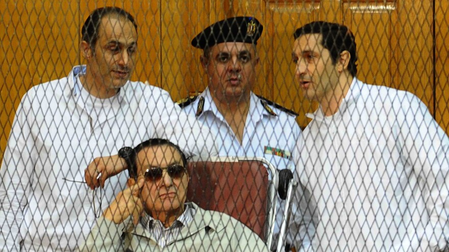 Hosni Mubarak (seated) and his two sons Gamal (left) and Alaa (right) stand trial in a courtroom cage in 2013.