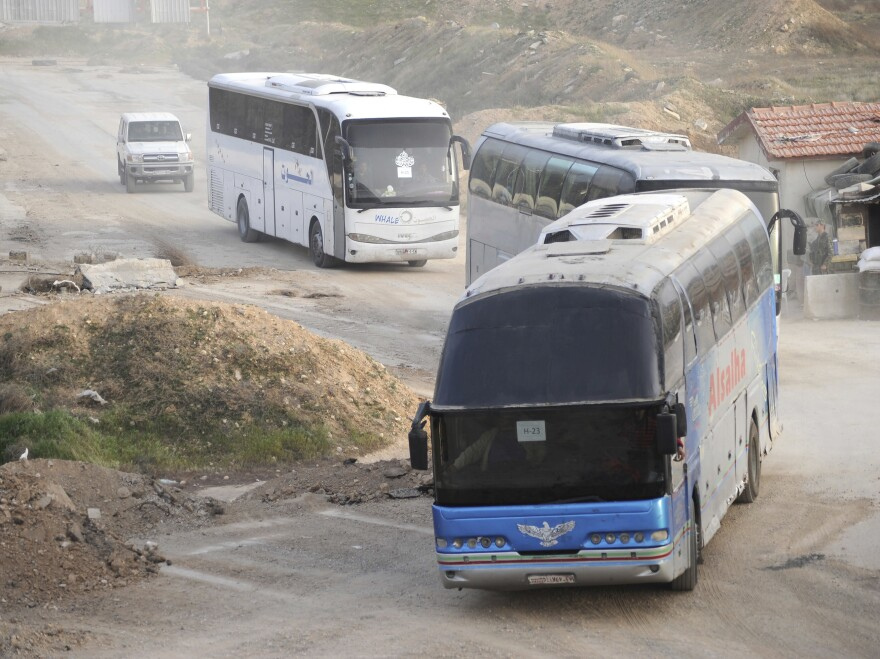 The evacuation by bus of rebel fighters and their families in eastern Ghouta, Syria. Buses from the Syrian Ministry of Transport and Syrian Red Crescent vehicles were seen on the outskirts of Harasta on Thursday, after crossing the last Syrian Army checkpoint before the town.