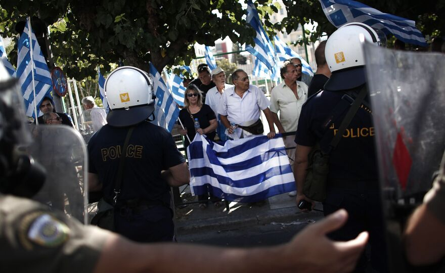 Riot police try to move supporters of the Golden Dawn party during a protest in solidarity of the arrested lawmakers in Athens on Saturday.