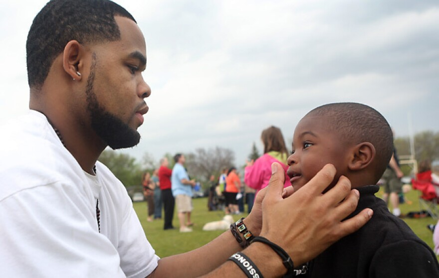 Joseph Arradondo assists his son Nasir, 2, on the sidelines of his daughter's soccer game in Brooklyn Park, Minn. Arradondo attended Co-Parent Court about a year ago and says the court helped with communication between him and Nasir's mother.