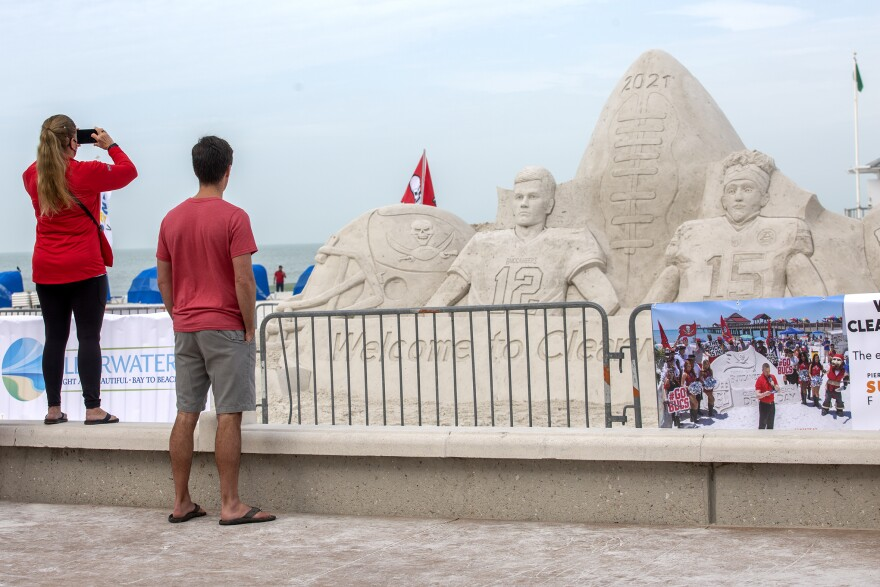 "two people wearing red shirts take photos of a Super Bowl Sand sculpture featuring two players, a Bucs helmet and a Chiefs helmet, and ""Welcome to Clearwater Beach."""