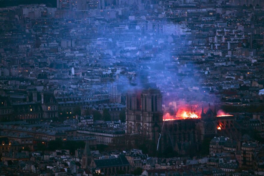 From Montparnasse Tower, flames and smoke can be seen billowing from the roof at Notre Dame Cathedral, about 2 miles away.