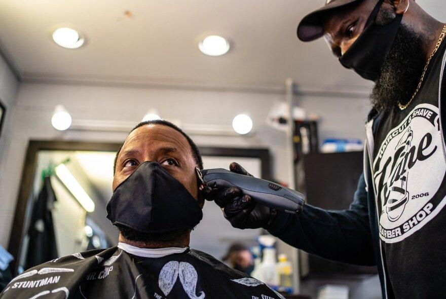 Barber wearing mask serving client wearing mask.