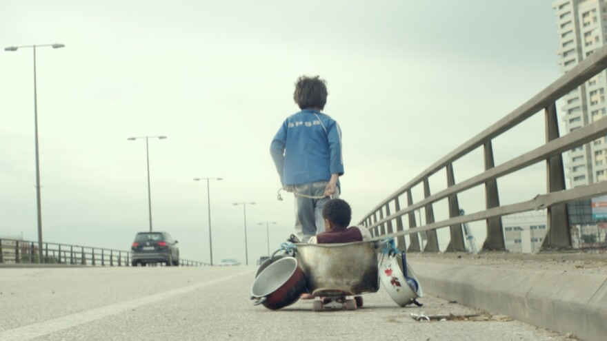 Zain (Zain Al Rafeea) pulls companion Yonas (Boluwatife Treasure Bankole) on a makeshift wagon in the movie <em>Capernaum.</em>