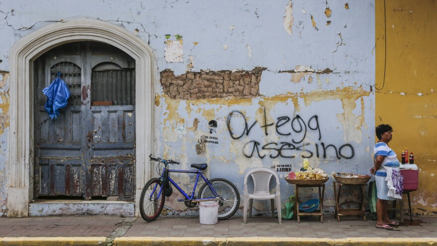 "A woman sells refreshments in front of graffiti that reads ""Ortega murderer!"" in Granada, Nicaragua, last week. The city's tourism industry has grown anemic since the wave of protests broke out in April."