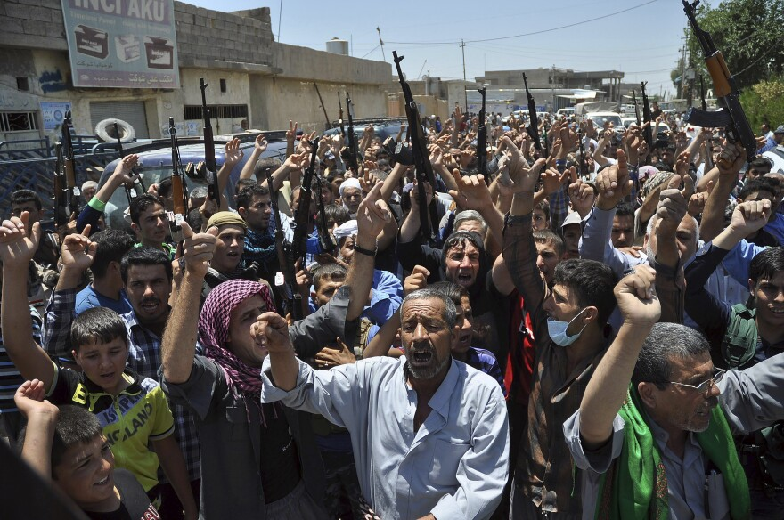 Mourners chant slogans against the al-Qaida breakaway group Islamic State of Iraq and Syria after they buried 15 bodies in the village of Taza Khormato in the northern oil-rich city of Kirkuk, Iraq on Monday.