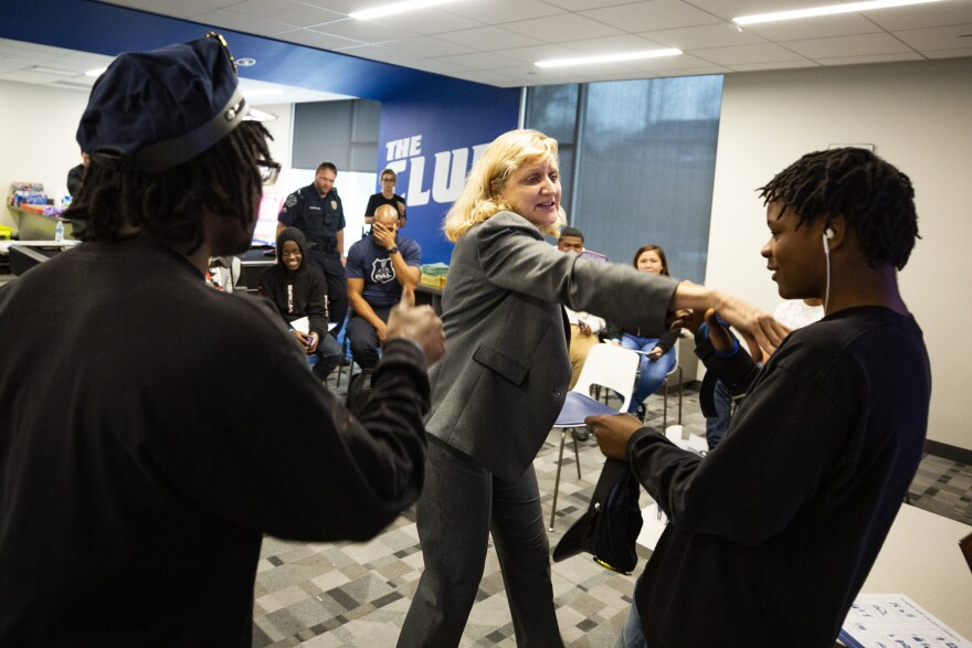 Thurau acts out a police officer interaction with student participant Azriel Griffin (right).