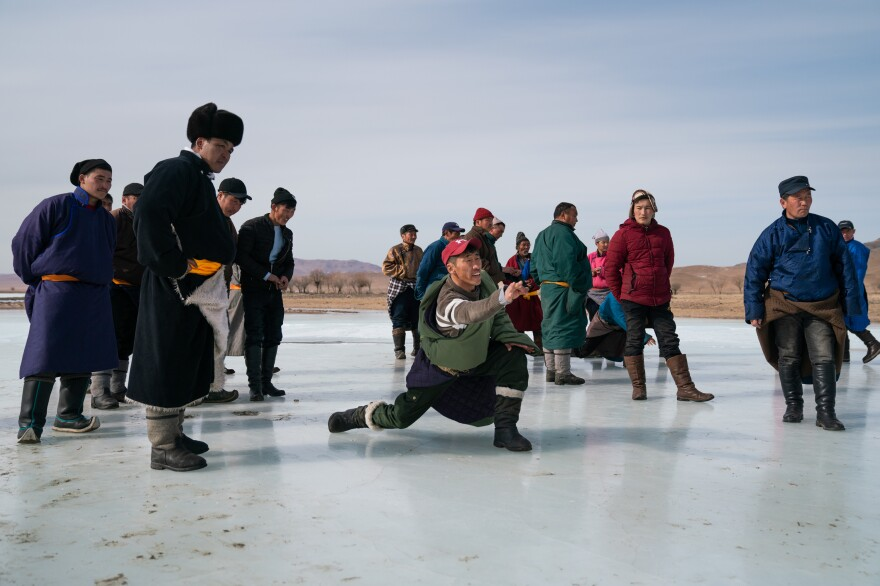 Mongolian herdsmen gather to play <em>musun shagai </em>(ice shooting) on the Tamir River in early March.