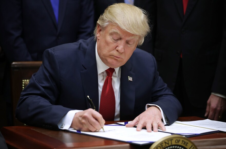 """President Trump signs the Veterans Choice Program Extension and Improvement Act at the White House in April. When they sign legislation, presidents can issue a """"signing statement"""" to share their legal interpretation of the new law. Trump did so with the Russia sanctions law."""