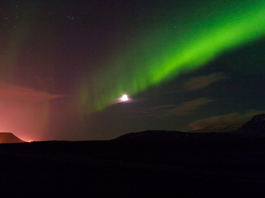 The northern lights over Iceland in February. The glowing orange area on the left side are the lights of the capital, Reykjavik.