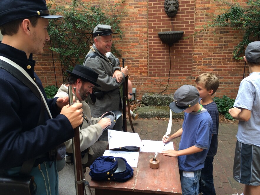 As Will Ruark, Jason Luker and Jay England look on, kids sign up to fight in a mock battle for the Confederacy or Union.