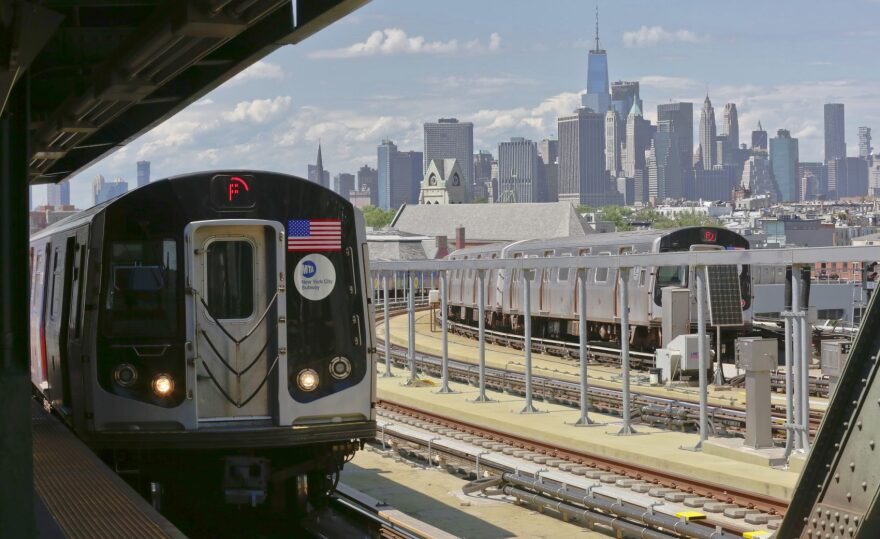 Subway trains at Brooklyn's Smith Street station travel above ground against a backdrop of the Manhattan skyline, Wednesday June 21, 2017, in New York. Subway riders are frustrated by power outages, signal problems and other breakdowns with the number of train delays tripled in five years. (Bebeto Matthews/AP)