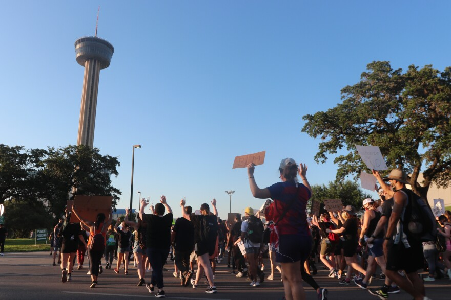 Protesters march toward the Tower of the Americas before heading farther into Hemisfair Park on June 8, 2020. The demonstrators gathered to protest the police killing of George Floyd in May 2020.
