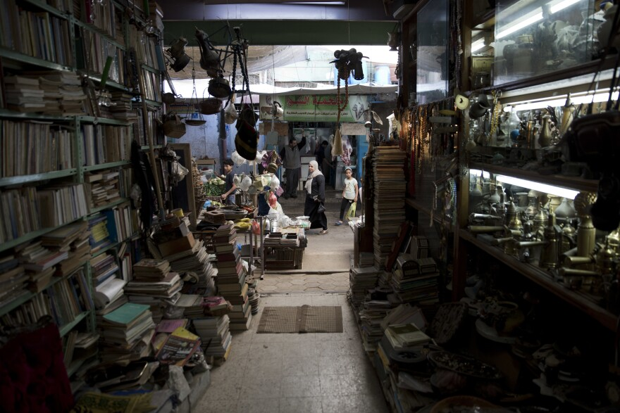 Palestinians pass by the Old Town Antique Store in Gaza's Old City, a shop brimming with dusty treasures, books, maps and ornaments.
