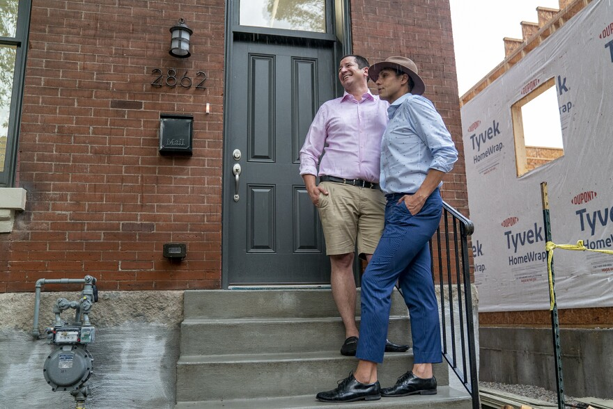 Sam and Omar Row stand outside their new Benton Park home on May 28. The two moved from Soulard in April, when the city's stay-at-home order was still in place. 05 28 2020