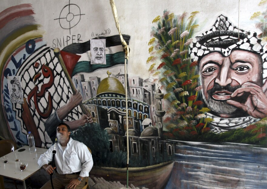 A Palestinian man smokes a nargileh (waterpipe) next to a mural of the late Palestinian leader Yasser Arafat in a coffee shop in the West Bank city of Jenin in September.
