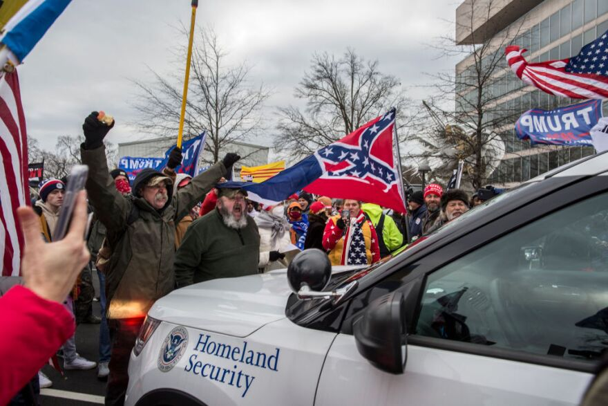 Trump supporters push back a police car while gathering outside the Capitol Building. (Probal Rashid/LightRocket via Getty Images)