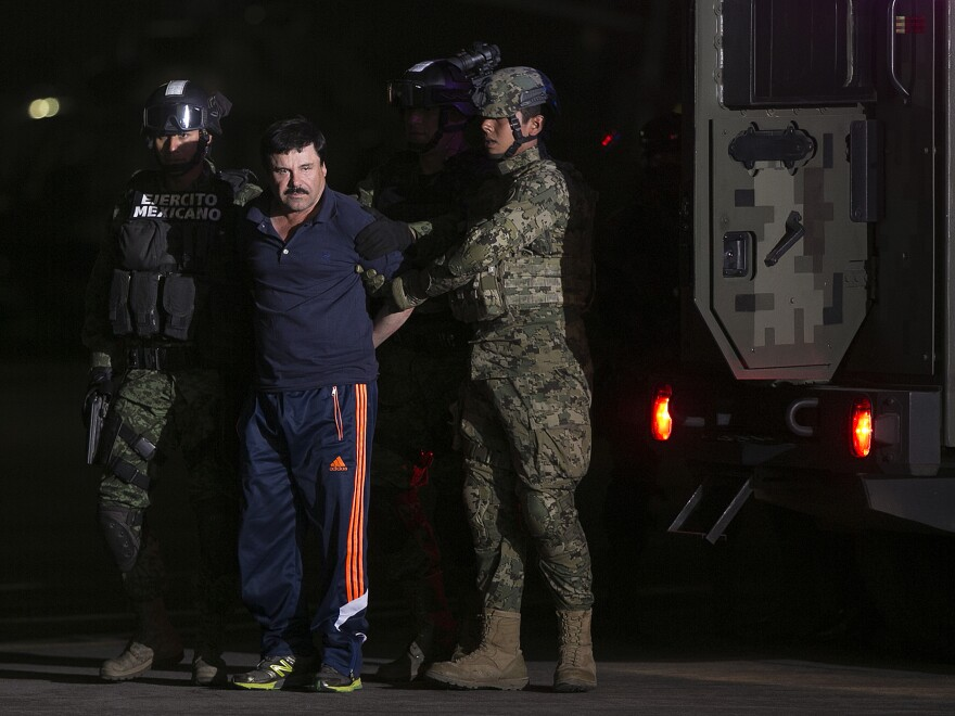 Joaquin 'El Chapo' Guzman, the world's most wanted-drug trafficker, second left, is escorted by Mexican security forces at a Navy hangar in Mexico City, Mexico, on Friday, Jan. 8, 2016.