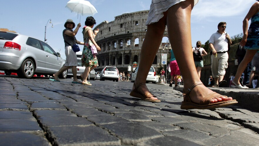 Pedestrians cross the cobblestone Via dei Fori Imperiali in front of Rome's Colosseum.
