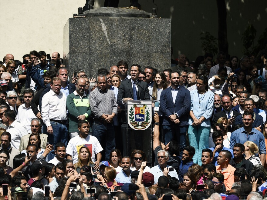 Venezuela's congressional leader, Juan Guaidó, is being recognized by a rising number of countries, including the U.S., as the South American country's interim president. Here, Guaidó (center) speaks to a crowd of opposition supporters at Bolívar Square, in eastern Caracas, last Friday.