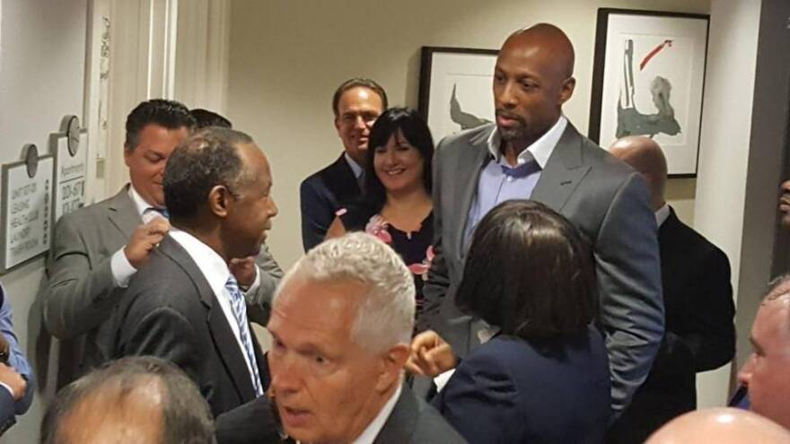 Housing and Urban Development Secretary Ben Carson emerges from a stuck elevator at Courtside Apartments Wednesday, as former NBA pro Alonzo Mourning looks on.