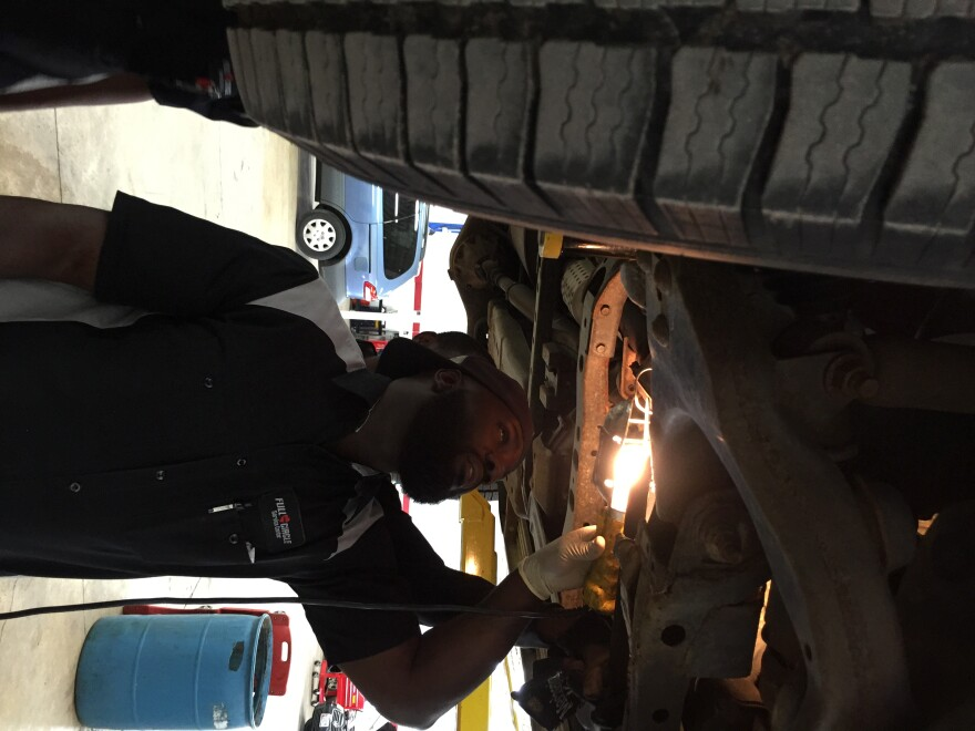 Antione Oglesby inspects a car at Vehicles for Change's service center.