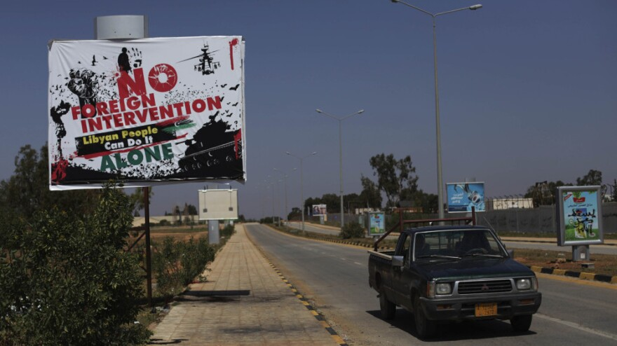"""A sign declaring  """"No foreign intervention, Libyan people can do it alone"""" stood outside the airport in Benghazi, Libya, on Monday."""