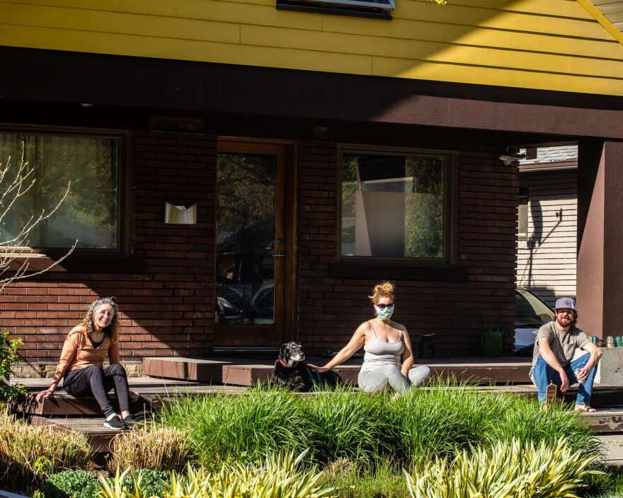 Photo of three people and a dog sitting on a front porch