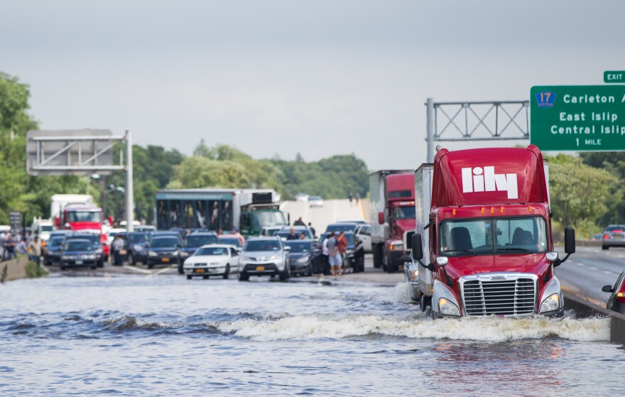 A trailer truck drives through a flooded Sunrise Highway in Islip.