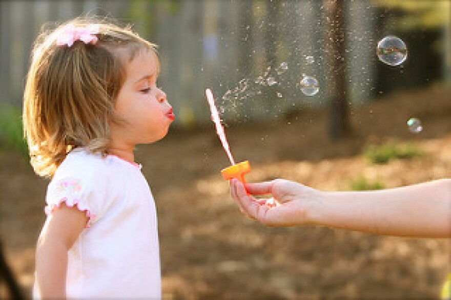 Young girl blowing bubbles outside
