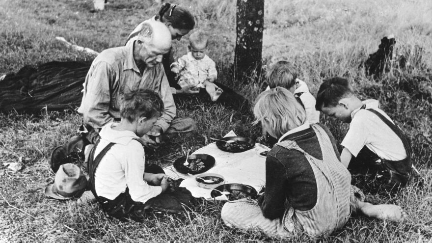 A migrant family saying grace before their noonday meal by the side of the road east of Oklahoma, 1930.