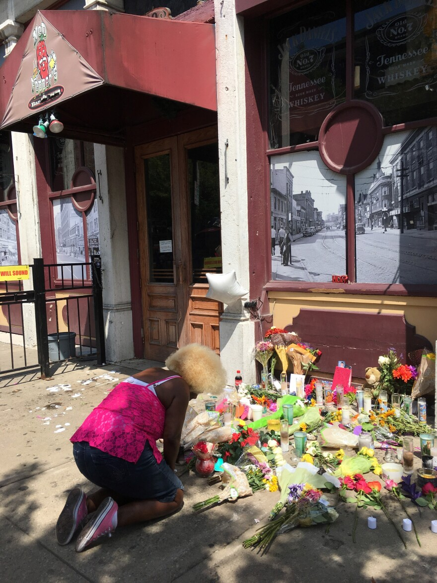 Annette Gibson Strong mourns in front of the makeshift memorial that was erected in front of Ned Pepper's bar after the mass shooting in Dayton. Strong became a fixture in the Oregon District, arriving each morning to clean and arrange the memorial.