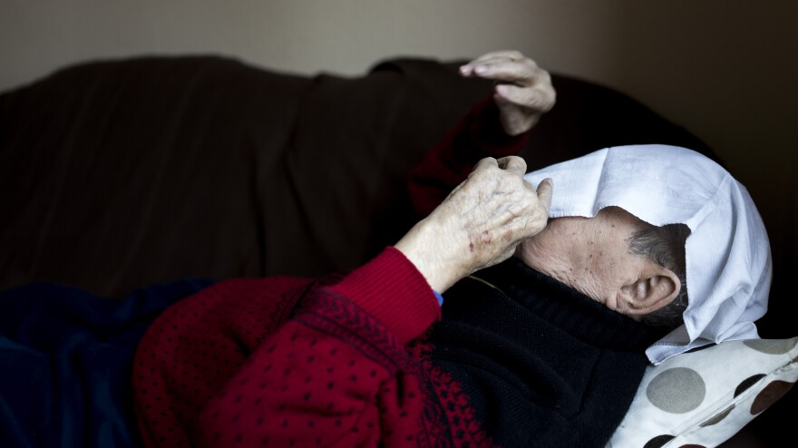 A towel covers the face of a man in a geriatric day care facility of the German Red Cross at Villa Albrecht in Berlin.