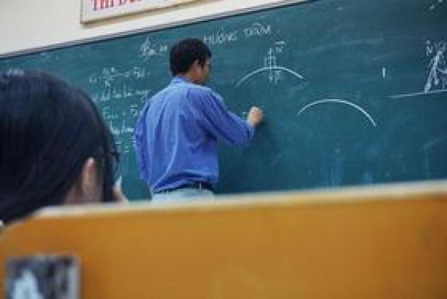 A physics teacher writes on his chalkboard in a classroom. (undated photo)