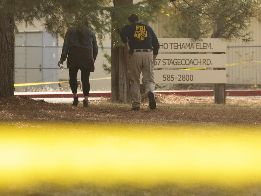 An FBI agent scans the area outside Rancho Tehama Elementary School, which went into lockdown during the shooting Tuesday. Tehama County, Calif., authorities credit that move with saving lives.