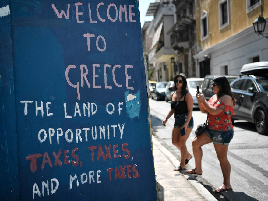 Tourists take pictures of slogans on a wall in central Athens on Satuday. Greece's third and final bailout officially ends on Monday after years of hugely unpopular and stinging austerity measures.