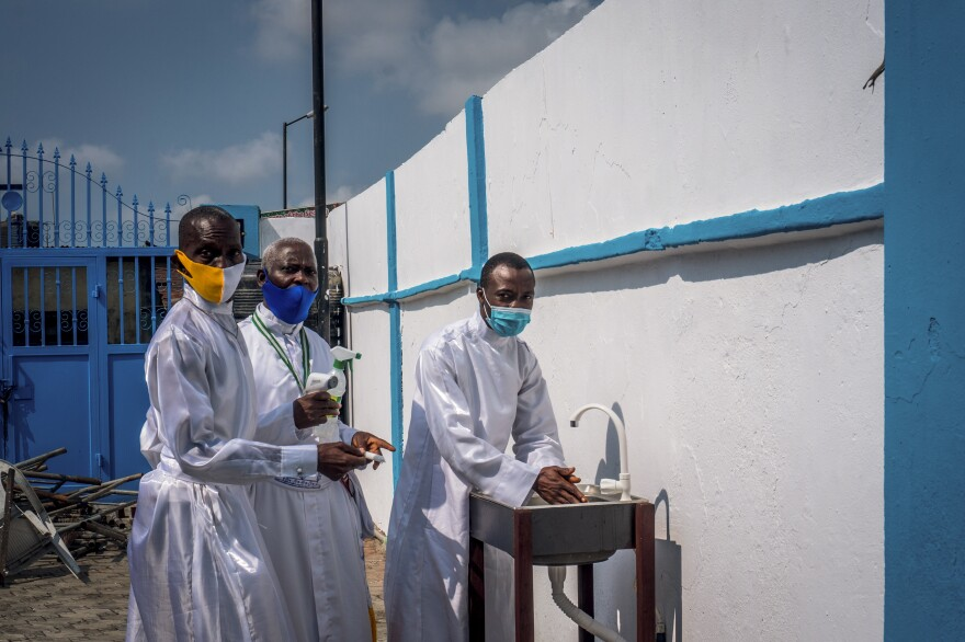 At the Celestial Church of Christ, church leaders guide a member to a handwashing station. When churches reopened earlier this year as Nigeria entered a new phase in its lockdown, they were instructed to provide worshippers with hand sanitizers and to ensure face masks are worn — even during services. <em>August 9. Lagos, Nigeria.</em>