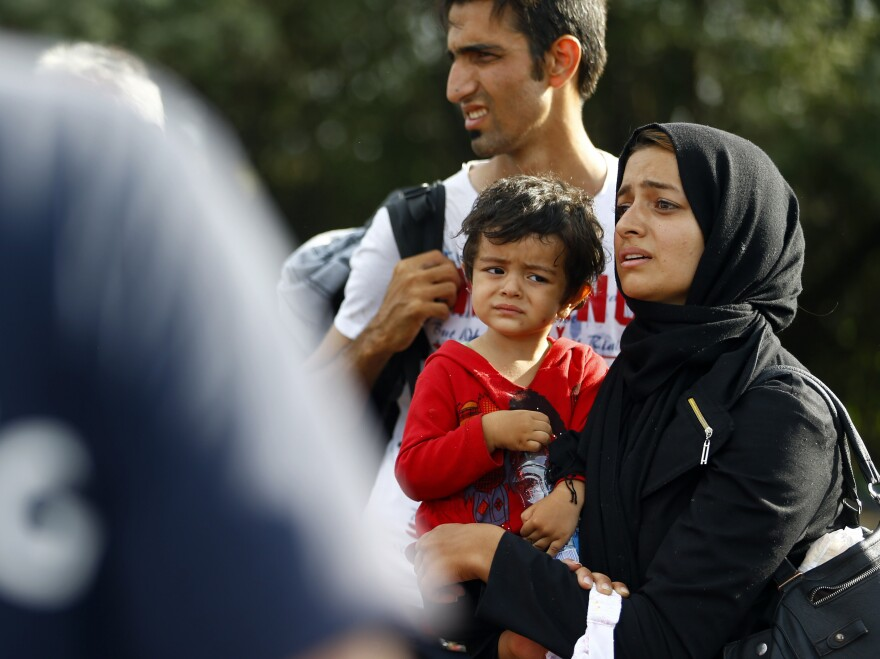 A migrant family stands at the border in Roszke, Hungary, after Hungarian police officers closed access between Serbia and Hungary on Monday.