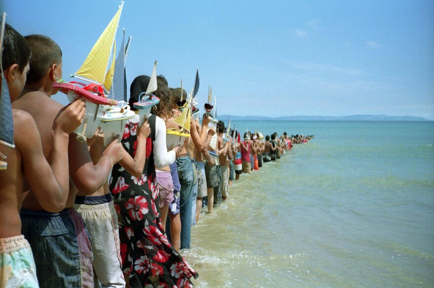 Children holding toy sailboats  disappear into the water in Francis Alÿs' 2008 video <em>Don't Cross the Bridge Before You Get to the River (Strait of Gibraltar, Morocco-Spain).</em>