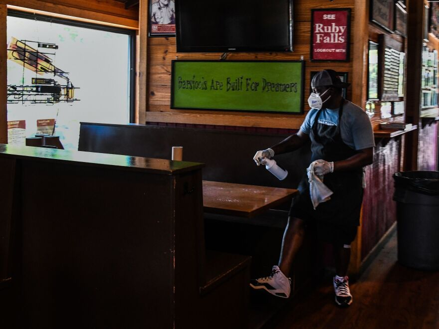 An employee of Moe's Original BBQ restaurant cleans the table after customers leave. Some Georgia restaurants reopened on Monday for limited dine-in service as the state loosened more coronavirus restrictions.