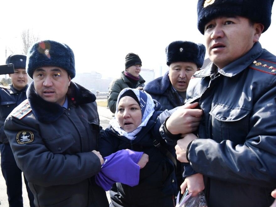 Kyrgyz policemen detain an activist of the Femen women's rights movement during the celebration of the International Women's Day in Bishkek, Kyrgyzstan, Sunday.