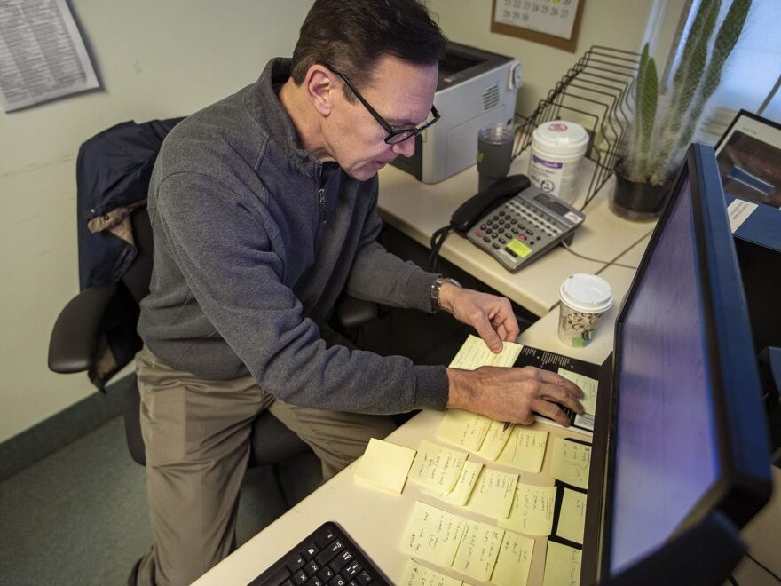 Army veteran Chris Riga survived multiple blast injuries in deployments in Afghanistan and Iraq. He rearranges sticky notes on his desk to assist him in remembering tasks he has to do throughout the day at his job as patient experience coordinator at the Northampton VA Medical Center in Leeds, Mass.