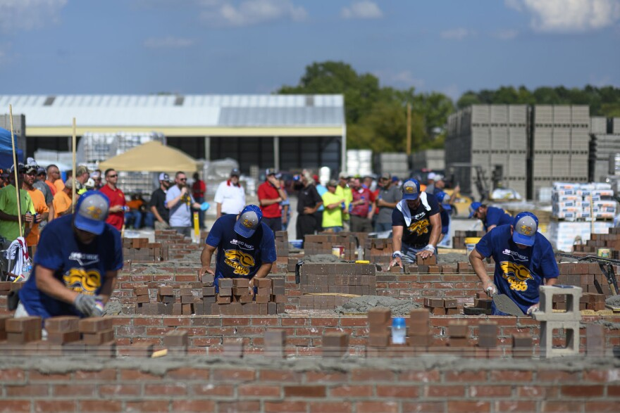 Masons scramble to finish building their walls during the fourth annual Bricklayer 500 competition on September 12, 2019. Teams of two worked to build the largest wall with the fewest possible errors in an hour.